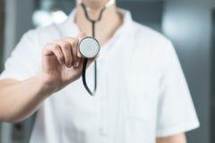 Jaskrawy zakończenie w górę samiec lekarki w mundurze z stetoskopem Słuchający stetoskop i trzymający kosmos kopii zdjęcie stock