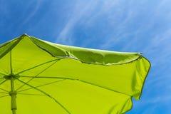 Jaskrawy - zielony parasol z niebieskiego nieba tłem Obraz Stock