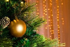 Jaskrawych złotych bożych narodzeń zabawkarski obwieszenie na zielonym drzewie obraz stock