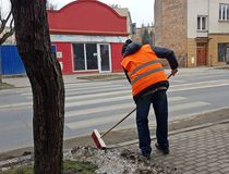 Jaslo/Poland-march 27,2018: The janitor in his working clothes sweeps the sidewalk. Cleaning of the territory in the city. The wor. K of the municipal public Stock Photo