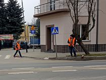 Jaslo/Poland-march 27,2018: The janitor in his working clothes sweeps the sidewalk. Cleaning of the territory in the city. The wor. K of the municipal public Royalty Free Stock Photo