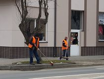 Jaslo/Poland-march 27,2018: The janitor in his working clothes sweeps the sidewalk. Cleaning of the territory in the city. The wor. K of the municipal public Royalty Free Stock Photos