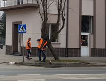 Jaslo/Poland-march 27,2018: The janitor in his working clothes sweeps the sidewalk. Cleaning of the territory in the city. The wor. K of the municipal public Stock Image