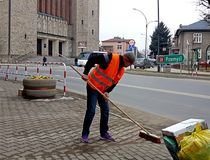 Jaslo/Poland-march 27,2018: The janitor in his working clothes sweeps the sidewalk. Cleaning of the territory in the city. The wor. K of the municipal public Stock Images
