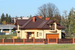 Jaslo, Poland - 9 9 2018: Project of a small villa with yellow walls and a brown roof. The back and front courtyard of the private. Territory enclosed by a stock image
