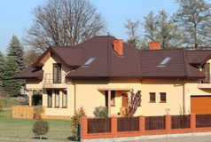 Jaslo, Poland - 9 9 2018: Project of a small villa with yellow walls and a brown roof. The back and front courtyard of the private. Territory enclosed by a royalty free stock photos