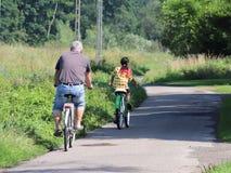 Jaslo, Polen - 9 juli 2018: De vader en de dochter berijden fietsen langs de asfaltweg amid de zomergreens in de stralen van royalty-vrije stock afbeelding