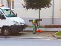 Jaslo, Polen - kan 25 2018: Een werknemer van de gemeentelijke dienst van de stad verwijdert het grondgebied Verbetering van het  royalty-vrije stock afbeeldingen