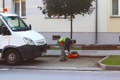Jaslo, Polonia - può 25 2018: Un impiegato del servizio municipale della città rimuove il territorio Perfezionamento dell'area in fotografia stock libera da diritti