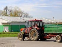Jaslo/Yaslo,波兰- 2018年4月14日:在拖拉机附近的两位农夫有在停车场的一辆拖车的在飞机棚附近 痛苦 图库摄影