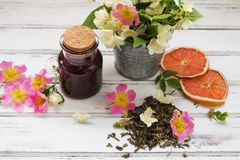 Jasmijn droge groene theebladen met jasmijnbloemen, met bloemen van wilde rozen en frambozenjam stock foto
