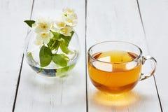 Jasmijnthee en jasmijnbloemen op een witte lijst Stock Fotografie