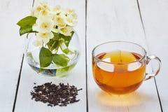 Jasmijnthee en jasmijnbloemen op een witte lijst Royalty-vrije Stock Fotografie