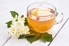 Jasmijnthee en jasmijnbloemen op een witte lijst Royalty-vrije Stock Foto