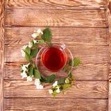 Jasmijnthee en jasmijnbloemen op houten achtergrond Stock Afbeeldingen