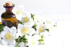 Jasminaromatherapyolja på vita plankor med blommor Royaltyfria Bilder