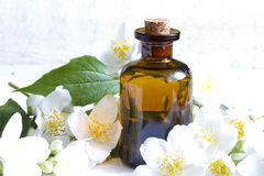 Jasmine aromatherapy oil on white planks with flowers. Concept Stock Photography