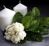 Jasmine and candles on dark background stock photos