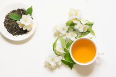 Jasmine dry green tea leaves with fresh jasmine flowers and cup of tea on white background. Stock Photo