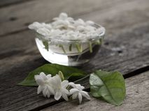 Jasmine floating in clear glass on wooden background stock images