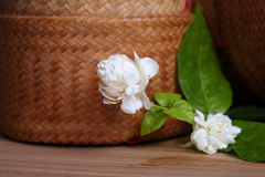Jasmine flowers and leaves on brown wooden board. royalty free stock photography