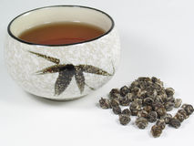 Jasmine Pearl Tea. A tea cup containing jasmine pearl tea with the loose tea spread next to it stock photography