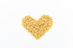 Jasmine rice arranged as a heart shape. Jasmine rice is placed on a white background Royalty Free Stock Image