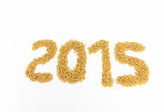 Jasmine rice brought organized into a number 2015. Jasmine rice is placed on a white background Stock Photos