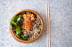 Wooden bowl filled with sweet brown rice. Hot spicy chicken for more same flavor. Jasmine rice cooked for lunch. Delicious hot spicy chicken. Awesome lunch for Stock Images