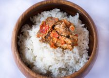Wooden bowl filled with sweet jasmine rice. Hot spicy chicken for more same flavor. Jasmine rice cooked for lunch. Delicious hot spicy chicken. Awesome lunch for Royalty Free Stock Photo