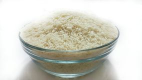 Jasmine Rice Grain. In the glass bowl on white background Stock Photos