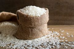 Jasmine rice in hemp sack on rustic wood background. Jasmine rice, also known as Thai fragrant rice or Khoa Hom Mali. Jasmine rice is delicious, nutty taste Royalty Free Stock Photography