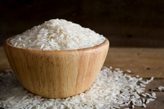 Jasmine rice in wooden bowl on rustic wood background. Jasmine rice, also known as Thai fragrant rice or Khoa Hom Mali. Jasmine rice is delicious, nutty taste stock image