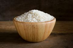 Jasmine rice in wooden bowl on rustic wood background. Jasmine rice, also known as Thai fragrant rice or Khoa Hom Mali. Jasmine rice is delicious, nutty taste Royalty Free Stock Image
