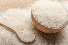 Jasmine rice in a wooden bowl, spoon on wooden background stock images