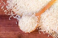 Jasmine rice in wooden spoon on wooden table (close-up shot). Jasmine rice grain, uncooked rice Stock Photo