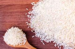 Jasmine rice in wooden spoon on wooden table (close-up shot). Jasmine rice grain, uncooked rice stock image