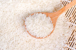 Jasmine rice in wooden spoon on wooden table (close-up shot). Jasmine rice grain, uncooked rice Stock Photos