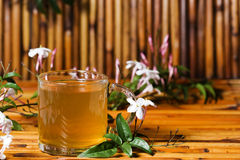 Jasmine Tea. A clear glass cup of jasmine tea resting on bamboo surface, jasmine leaves and flowers around cup and blurred in background Stock Photos