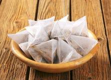 Jasmine tea bags. Pyramid-shaped jasmine tea bags in wooden bowl Stock Photos