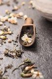 Jasmine tea in dark wooden scoop on black stone background, close up Stock Image