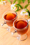 Jasmine tea. Glass cups of jasmine tea and sprig of jasmine Stock Photos