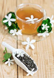 Jasmine tea. Green tea with jasmine blossom in cup and ceramic scoop. Selective focus Royalty Free Stock Photo