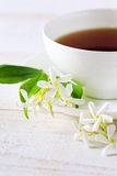 Jasmine tea in a white bone china cup on white background. Focus selective stock images