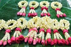 Jasmingirland med rosa färgrosen på bananbladet. Arkivbild