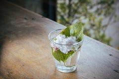 Jasminum im Glas auf dem Holztischhintergrund mit Steigung Stockbild