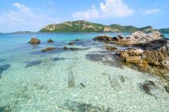 Jasna błękitna woda morska z kamienną i dużą górą. obraz royalty free