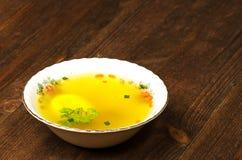Jasna polewka z warzywami w talerzu na drewnianym stole Nieociosany styl Obrazy Stock