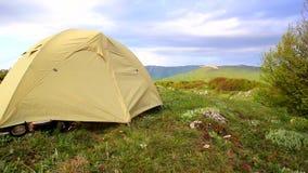 Jasnożółty namiot kiwa w silnym wiatrze przy pięknym ranek góry krajobrazem zbiory