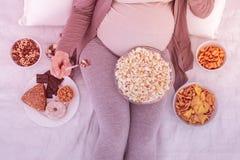 Jasnogłowa atrakcyjna kobieta w ciąży w wygodnym odzieżowym łasowaniu przekąsza zdjęcia stock